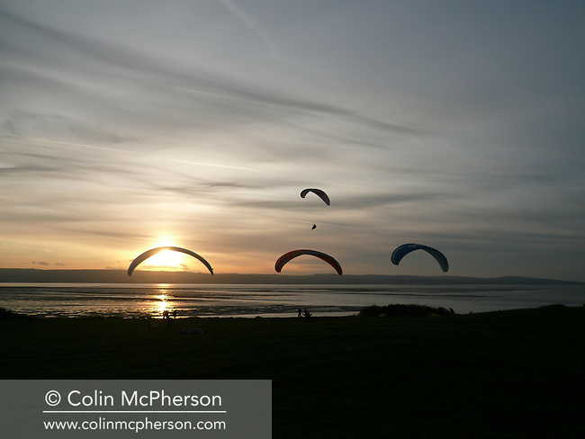 Members of the North Wales Paragliding Club, flying above the Dee Esturay in Wirral, northwest England during a club meeting. Paragliding was a recreational and competitive flying sport where the pilot sits in a harness suspended below a fabric wing, whose shape is formed by the pressure of air entering vents in the front of the wing. A paraglider was a free-flying, foot-launched aircraft and the wing or canopy is known in aeronautical engineering as an airfoil or parafoil.