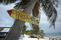 Belize, Central America - Sign points the way to a bar patio for the party crowd on Caye Caulker