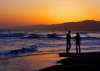 Couple In Love Walking Along Beach
