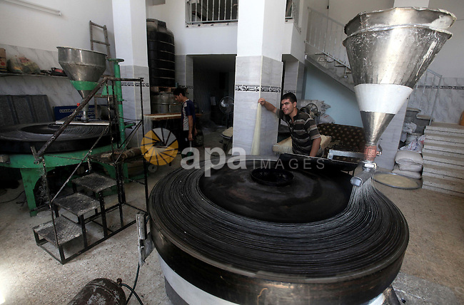 """Palestinians make Konafa in Gaza city on 28 July 2012. Palestinians gets ready for break their fast """"Eftar"""" after long hours of fasting. Bakers make Konafa and  traditional pastry known as ''Qatayef'' which is consumed during Ramadan. Photo by Majdi Fathi"""