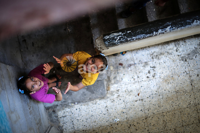 Riham and Hanin Zidan, 8-year-old, a Palestinian twins play at their home at al-Shati refugee camp, western Gaza City, Aug 12, 2013. The mother of Riham and Hanin faced a hard time conceiving a baby for a 15 years of marriage before they are born naturaly. Photo by Mahmoud Hamda