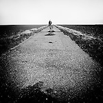 Lone figure on road, hiking with backpack