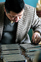 A worker sorts and boxes a roll of harmonicas at the Shanghai General Harmonica Factory (SGHF) in Shanghai, China. Although it makes well-respected brands such as the Huang, Suzuki, and Hohner that are favored by many professional musicians around the world, the 60 years old state owned SGHF had to trim down its work force from 800 in the mid 1980's to just over 100 today..23-FEB-04