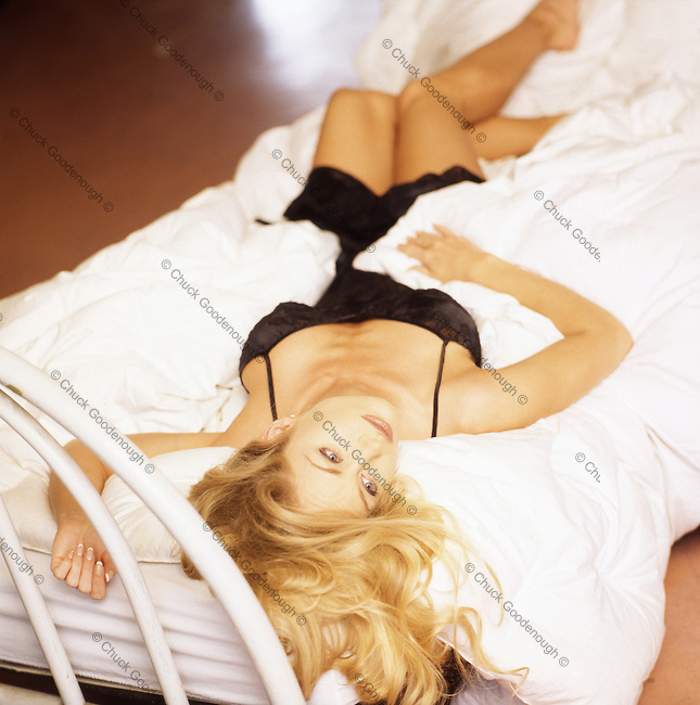 Stock Photo of Blond Woman on a Bed in Black Lingerie