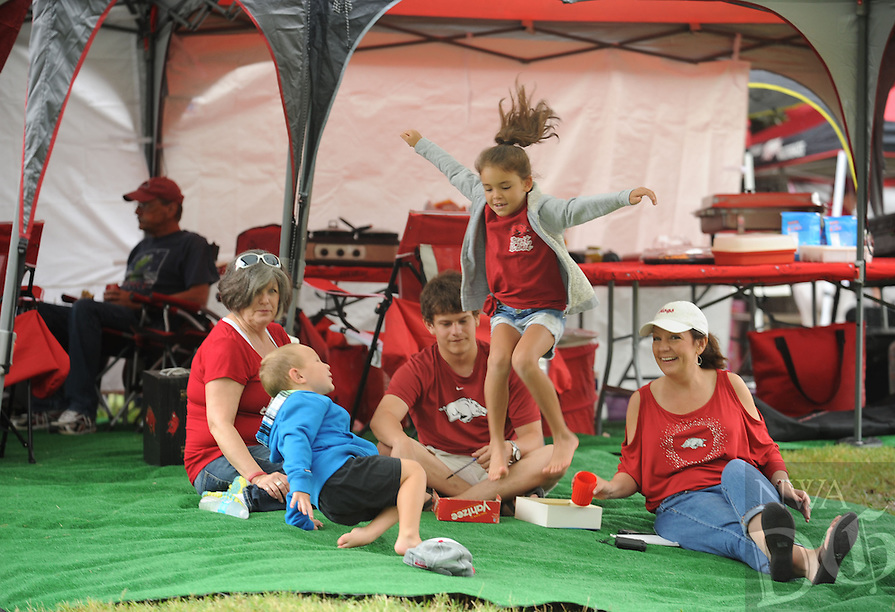 STAFF PHOTO ANDY SHUPE - Evey Tomlinson, 7, of Gentry, center, leaps onto a carpet alongside her grandmother Donna Tomlinson of Gentry, left; her brother, Cooper Tomlinson, 3; and other family members Cory Spencer and his mother April Gage, both of Fayetteville, play a game of Yahtzee while tailgating prior to the start of the University of Arkansas' football game with Nicholls State Saturday, Sept. 6, 2014, at Razorback Stadium in Fayetteville.