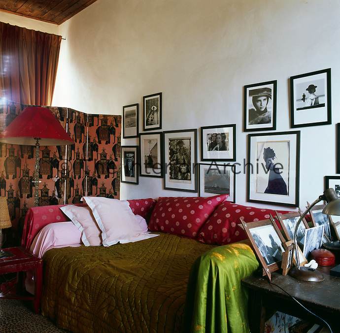 In an informal bedroom a collection of black and white photographs hangs on the wall over a bed draped with pink and green fabrics.