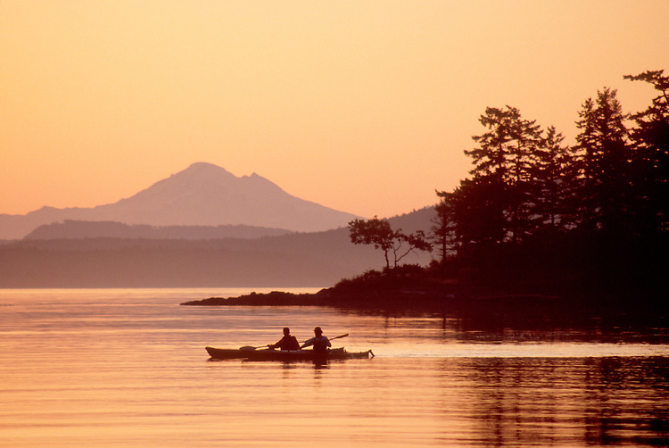 Sea kayakers, San Juan Islands, Mount Baker, Pacific Northwest, Washington State, Sunrise, Haro Strait, foreground: Gulf Islands British Columbia, Canada