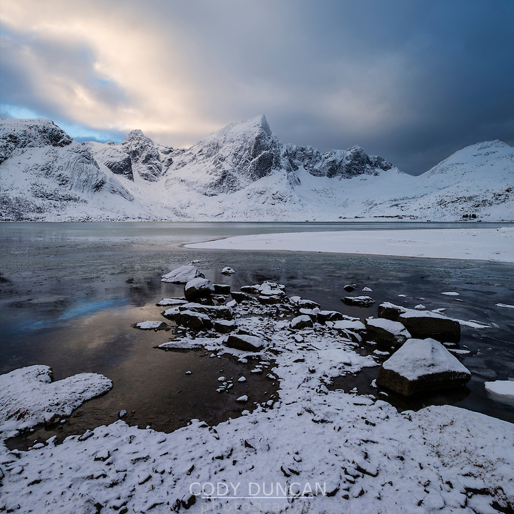Stortind mountain peak rises over winter coastline at Flakstadpollen, Flakstadøy, Lofoten Islands, Norway