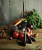 an assortment of vegetables on a rustic wooden table. Vegetables include onion, tomatoes, carrots and aubergine