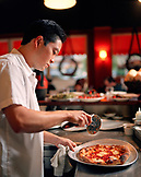 USA, California, Los Angeles, chef cutting pizza at Pizzeria Mozza restaurant