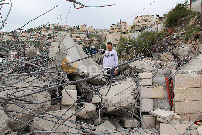 A Palestinian boy stands on the rubble of his family house that was demolished by Jerusalem municipality workers in Jerusalem on Jan. 07, 2016. Israeli police Thursday demolished two Palestinian-owned homes in Ein el-Lawza neighborhood in Jerusalem, citing construction without a permit as a pretext, according to local sources. Photo by Mahfouz Abu Turk