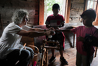 NWA Democrat-Gazette/CHARLIE KAIJO Karen Chotkowski of the Wool and Wheel Hand Spinners Guild (left) gives a piece of wool to Gabriel Ramirez 9 (right) as Eduardo Montes, 9, (center) watches during the Sheep to Shawl event, Thursday, October 4, 2018 at the Shiloh Museum in Springdale.<br />
