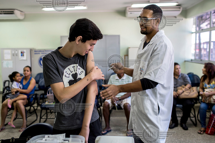 Health worker Tiago Nunes gives a yellow fever vaccination to Giovanni Barone, 14, at a public clinic, Unidade de Saude - Praia do Sua. As the worst yellow fever epidemic in decades continues to expand, cities such as Vitoria are vaccinating their residents in an attempt to halt the spread of the disease.