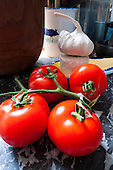 Wincombe, Dorset, England. Tomatoes and garlic  on marble surface in the kitchen.