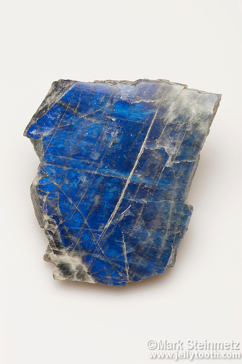 Labradorite is a feldspar mineral of the plagioclase series. As a result of light refraction, it shows an iridescent brilliant blue when viewed at the right angle, similar to that of certain butterfly scales as in a Blue Morpho, and certain bird plumages as in North American Tree Swallows. Sydney Mines, Labrador.