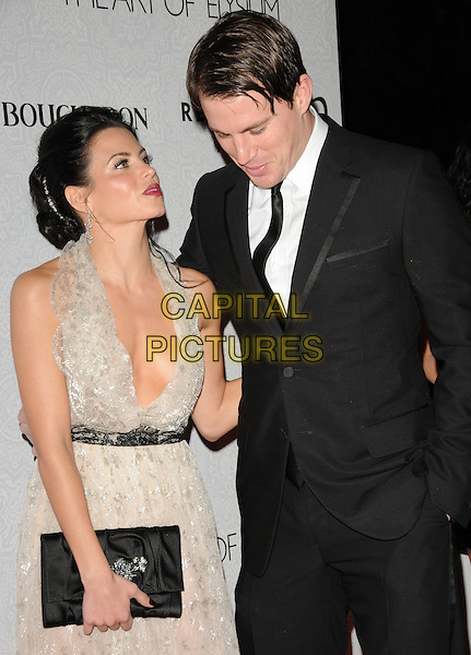 "JENNA DEWAN & CHANNING TATUM.Art of Elysium 3rd Annual Black Tie charity gala '""Heaven"" held at 990 Wilshire Blvd in Beverly Hills, California, USA, .January 16th 2010 .half length dress low cut plunging neckline cleavage clutch bag halterneck black white lace grey gray black suit jacket hand in pocket married husband wife looking up down profile .CAP/RKE/DVS .©DVS/RockinExposures/Capital Pictures"