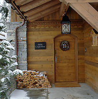 The snow-dusted entrance to the chalet where newly cut logs have been neatly stacked