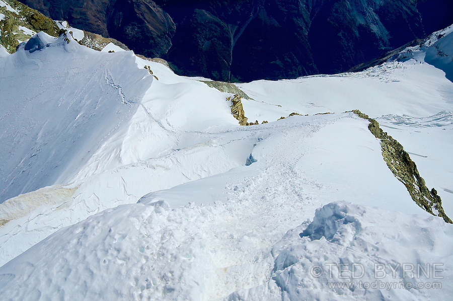 Summit view of narrow snow path on high mountain in the Swiss Alps