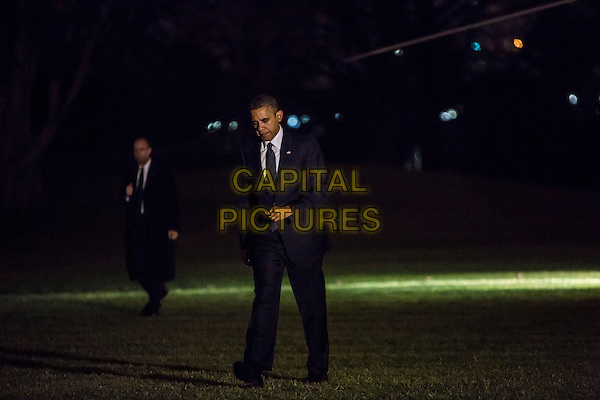 United States President Barack Obama returns to the White House after traveling to Connecticut on Sunday, December 16, in Washington, DC. President Obama met with first responders and the families of victims of the shooting at Sandy Hook Elementary School in Newtown. .full length black suit.CAP/ADM/CNP/BH.©Brendan Hoffman/CNP/AdMedia/Capital Pictures