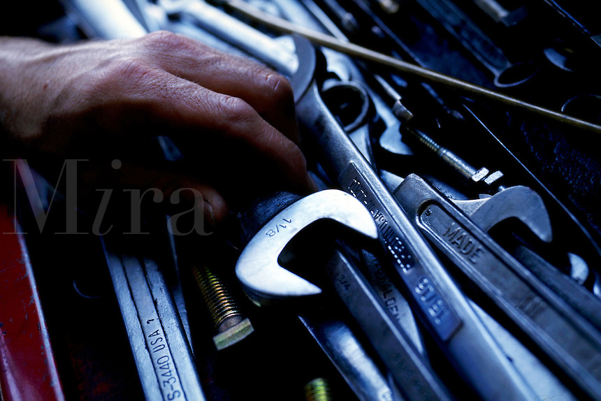 A mechanic grabs a wrench from a tool box. Mechanic.