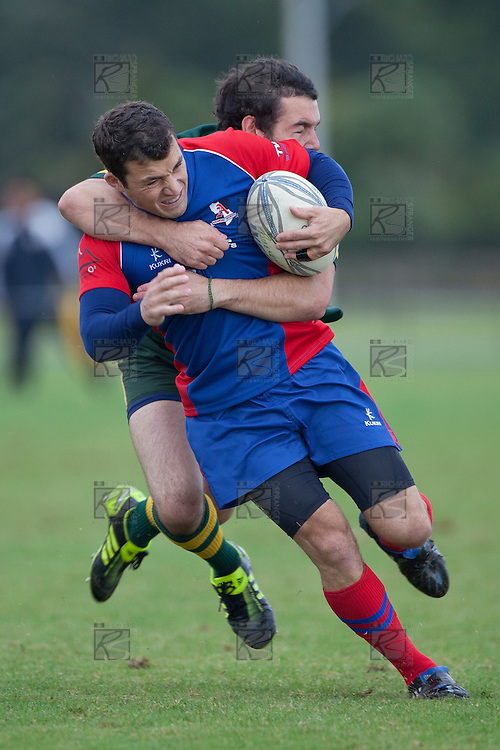 Dean Morris wraps up Cameron Bell in a tackle during the Counties Manukau Premier Club Rugby game between Ardmore Marist and Pukekohe, played at Bruce Pulman Park Papakura, on April 16th 2011..Ardmore Marist won 23 - 16 after leading 23 - 6 at halftime.