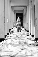 A woman looks through a line of dead bodies that were extracted from the collapsed Rana Plaza building in hopes of identifying her relative in Savar, near Dhaka, Bangladesh.