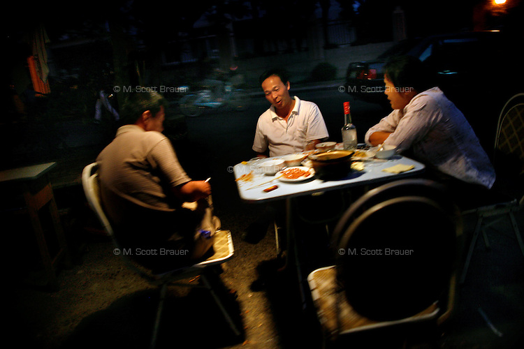 Men sit outside of a restaurant after a meal in Nanjing, China.