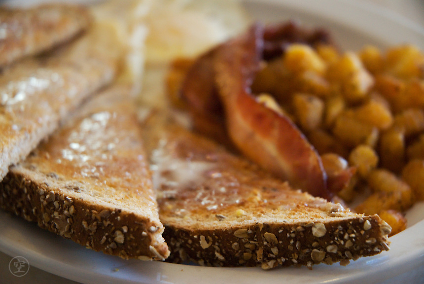 Eggs over easy, bacon, homefries, and multi-grain toast make up a typical, if unhealthy, North American breakfast, served at an Ontario diner.