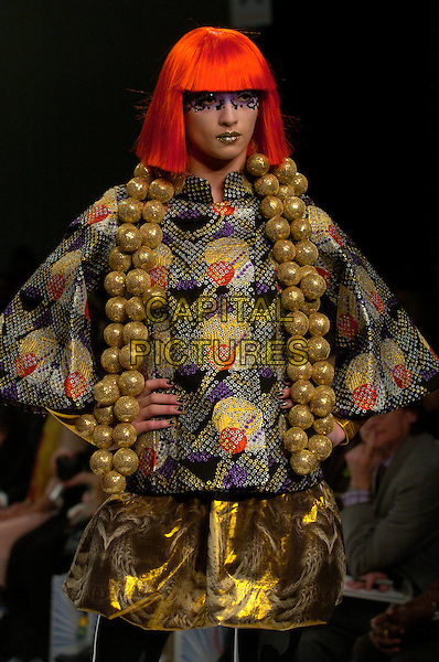 MODEL.The Autumn / Winter 2007 collection of Indian designer Manish Arora at London Fashion Week (LFW), London, UK..February 12th, 2007.runway catwalk wig half length make up make-up makeup black gold print jewel encrusted balls necklaces.CAP/CAN.©Can Nguyen/Capital Pictures