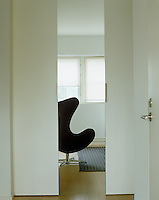 View through open sliding doors to an Arne Jacobsen egg chair upholstered in hide