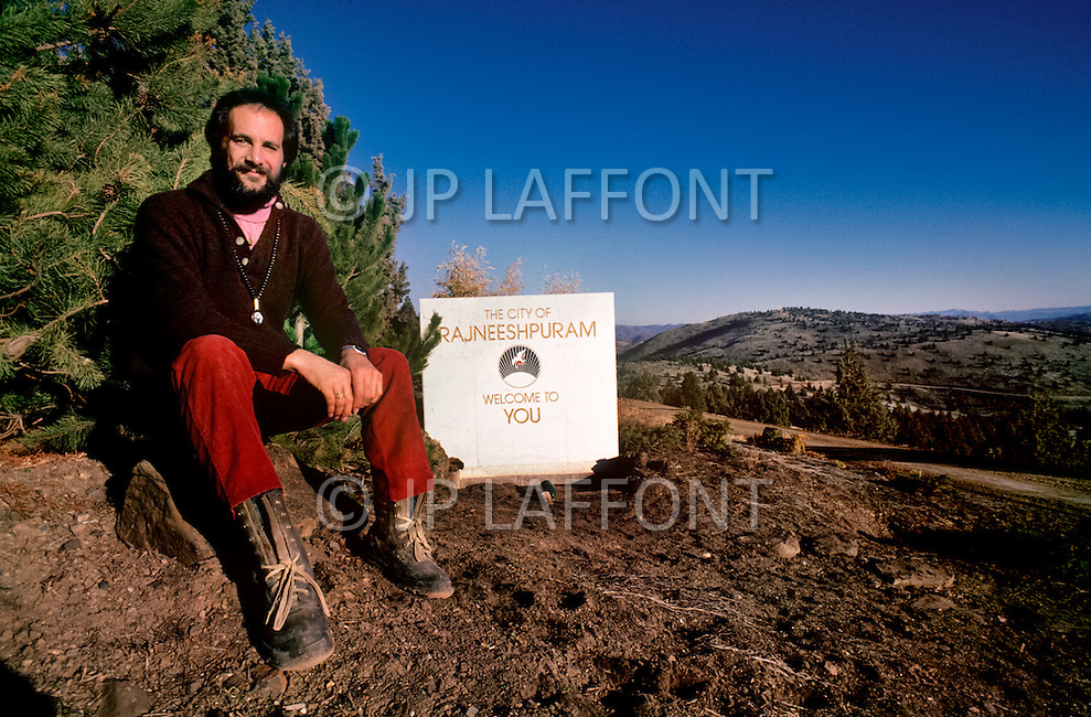 Wasco, Oregon, February 1984:Swami Krishna Deva, Master of the Rajneeshpuam Community, in front of the sign indicating the entrance to the town.  Rajneeshpuram, was an intentional community in Wasco County, Oregon, briefly incorporated as a city in the 1980s, which was populated with followers of the spiritual teacher Osho, then known as Bhagwan Shree Rajneesh. The community was developed by turning a ranch from an empty rural property into a city complete with typical urban infrastructure, with population of about 7000 followers.