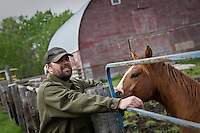 Yves Breton pets a Percheron horse on a farm in Saint-Laurent, Manitoba Monday May 23, 2011. The Percheron is a breed of draft horses that originated in the Perche valley in northern France.