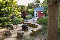 Permeable patio with stone bench and outdoor fireplace and tool shed in Habets garden, Pleasant Hill, California