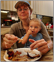 A grandmother holds her grandson while eating BBQ. Model released image can be used to illustrate many purposes.