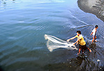 Fisherman casting his net off the beach in Apia, Samoa, USA 1980