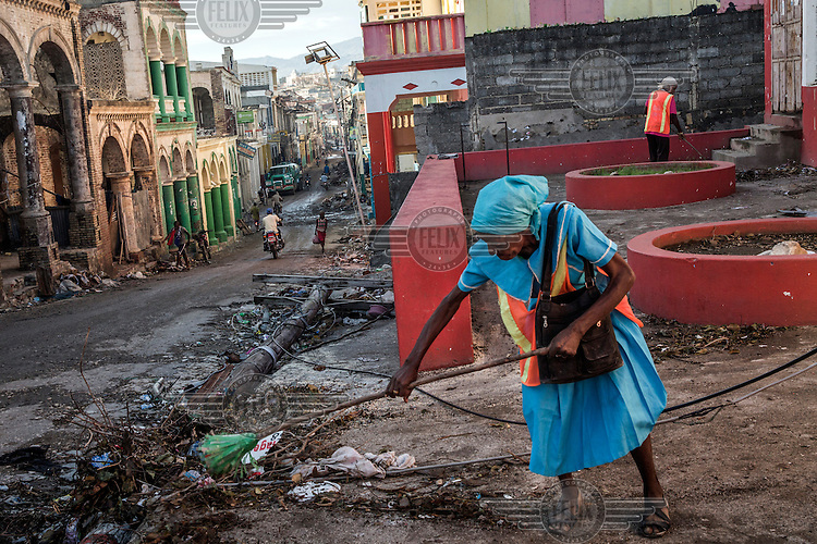 A woman sweeps debris into a pile at the side of a street in the town of Jeremie which suffered severe damage after Hurricane Matthew hit the the southwest peninsula. Hurricane Matthew, the first category 5 Atlantic hurricane since 2007, hit the island on 4 October 2016. Winds of up to 230km/h (145mph) tore across the worst affected areas, mainly in the south of the island, killing around over 1,000 people and leaving hundreds of thousands in need of assistance.