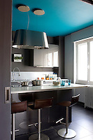 The ceiling of the kitchen has been painted a deep cerulean blue offsetting the grey of the walls, cupboards and floor