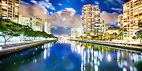 A full moon rising behind clouds above the Ala Wai Canal, Honolulu, O'ahu; buildings glow on both sides of the canal in this 30-second long-exposure image.