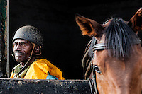 Veteran Jockey David Mwikya waits to take a horse for morning exercise. Mwikya began racing at Ngong in the 1980's. Now retired he continues as a work rider in the stables. Ngong Racecourse, Nairobi, Kenya. March 13, 2013. Photo: Brendan Bannon