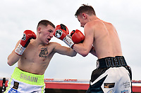Shaun Cooper (white/green shorts) defeats boy Jones Jnr during a Boxing Show at Stevenage Football Club on 18th May 2019