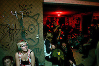 Concert-goers wait between bands at a punk concert in the White House in Woodstock, Illinois.  The White House was a small suburban residential home rented by a group of 20-somethings in Woodstock, Illinois, a distant northwestern suburb of Chicago.  For about a year, the renters of the house staged punk-rock concerts in the house's small basement, without the approval of the neighborhood, local government, or police.  .