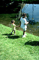 Two African American sisters age 6 and 2 looking into Loring Park Pond.  Minneapolis Minnesota USA