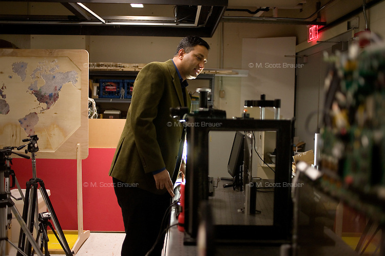 Dr. Ramesh Raskar, part of the Media Lab Camera Culture group, set up equipment in a lab at MIT in Cambridge, Massachusetts, USA.  Velten and Raskar's group has developed a camera that records at 1 trillion frames per second, which allows, for example, the recording of pulses of light moving through a liquid.