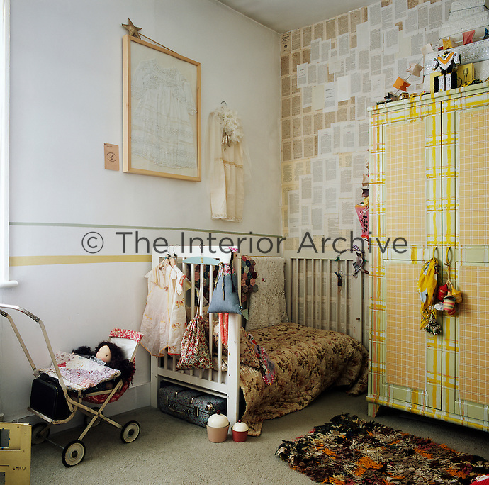 A child's bedroom with a white cot in one corner and small painted wardrobe against one wall. A vintage child's pram stands near the cot.