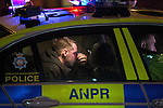 © Joel Goodman - 07973 332324 . No syndication permitted . 20 December 2013 . Manchester , UK . A man sits in the back of a police car at the scene of a collision between a car and a woman in the road . A Mad Friday shift with Inspector Matt Bailey-Smith , of Greater Manchester Police's ANPR and Tactical Vehicle Intercept Unit . Photo credit : Joel Goodman