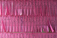 The pink tissue paper prayer flags, contain the names of people who have made donations for the upkeep of the temple, Chua Thien Hau Temple, Ho Chi Minh City, Saigon, VietnamThien Hau Pagoda. Cholon, Ho Chi Minh City, Saigon<br />