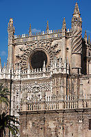 Low angle view showing the Puerta de San Cristobal or del Principe and pinnacled walls, Seville Cathedral, Andalucia, Spain, pictured on December 27, 2006 in the midday winter light. Seville Cathedral is the largest Gothic building in the world. It was converted from the original 12th century Almohad Mosque on this site during the 16th century and the original Moorish entrance court and Giralda Minaret are both integrated in the cathedral. Inside is the tomb of the explorer Christopher Columbus (1451-1506). Picture by Manuel Cohen