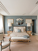 An elegant, luxurious bedroom in tones of blue grey and neutral furnishings. Two stylish lamps stand on bedside tables either side of a double bed with an upholstered headboard.