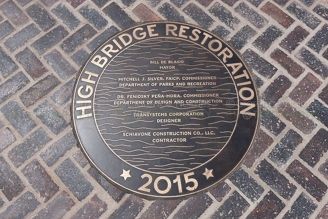 Bronze sidewalk medallion with historical information in the walkway of the High Bridge connecting Manhattan with the Bronx over the Harlem River in New York City.