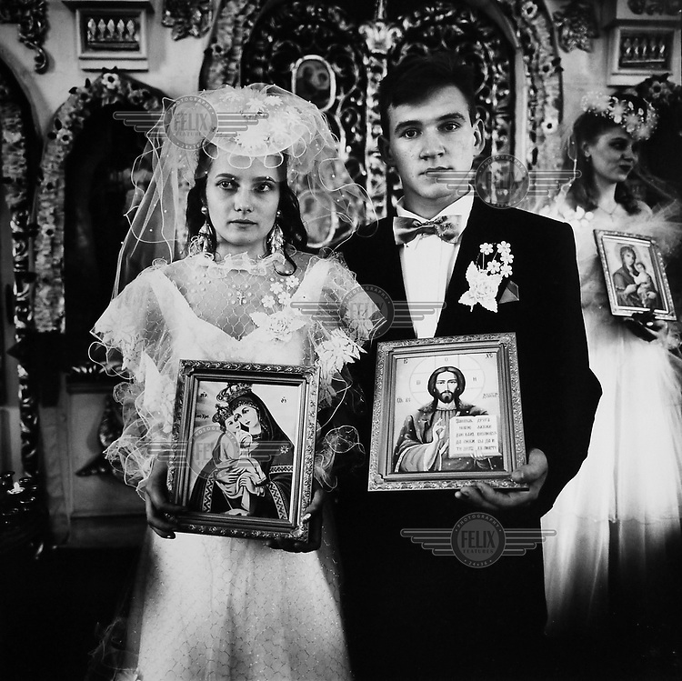 Irina Slakar and Demitri, both holding icons, at the local Russian Orthodox church on their wedding day.